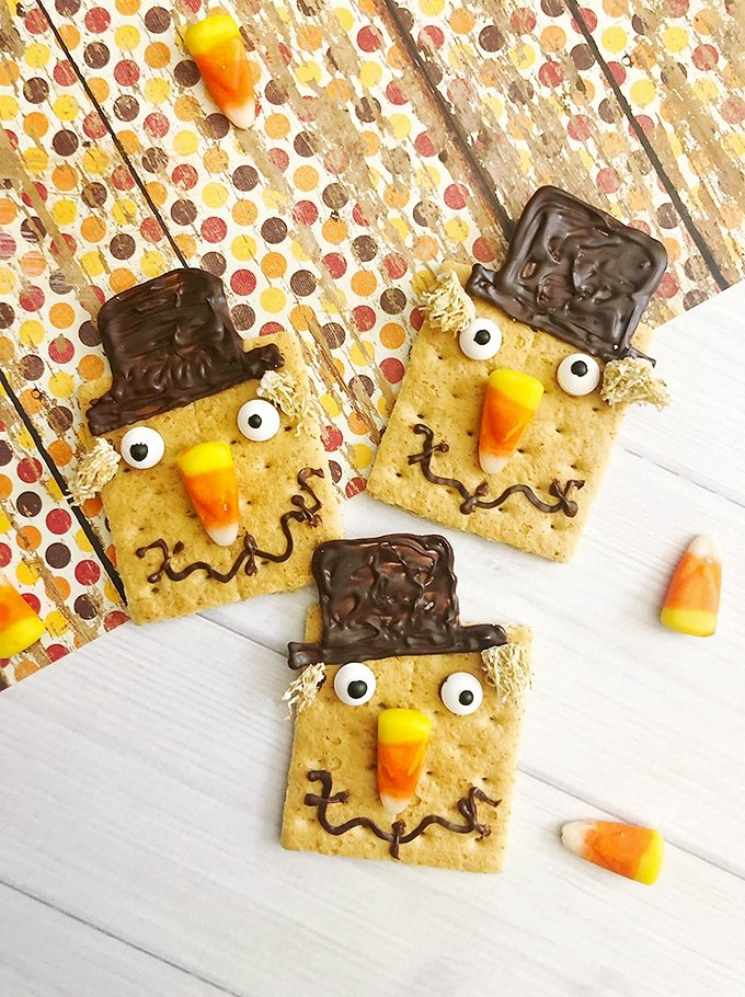 Graham crackers decorated as scarecrows with candy corn, melted chocolate and mini wheaties.