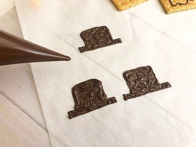 drawing scarecrow hat on parchment paper with melted chocolate