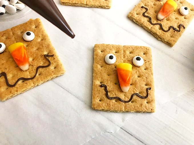 Graham crackers decorated as scarecrows are super fun for any fall treat!