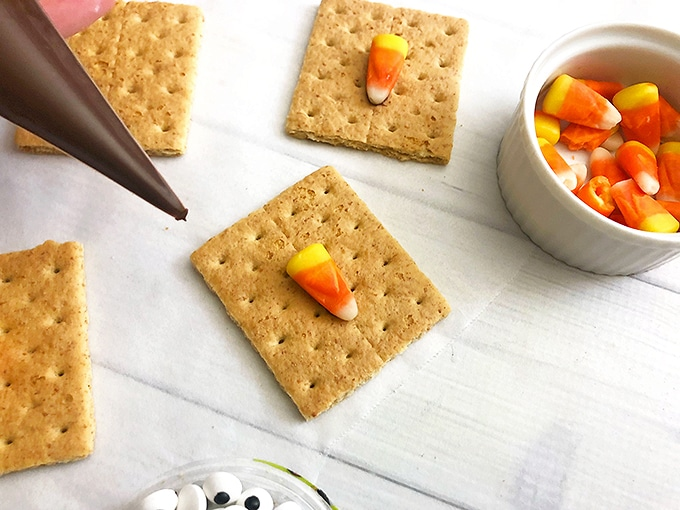 sticking candy corn on graham crackers to resemble a scarecrow nose
