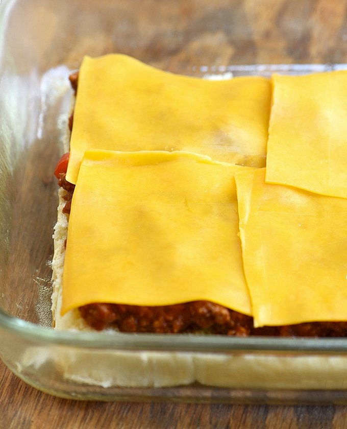 sliced bread slab topped with sloppy joe beef mixture and sliced cheddar cheese in a casserole dish