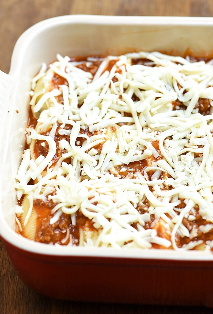 stuffed pasta shells with meat sauce and shredded mozzarella in a casserole dish ready to bake