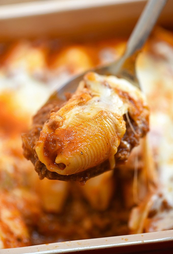 cheese stuffed jumbo pasta shells with meat shells on a serving spoon