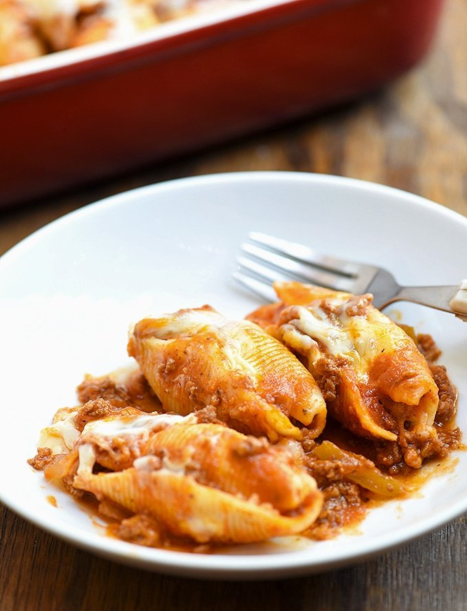 Jumbo pasta shells with ricotta filling and meat sauce on a serving plate