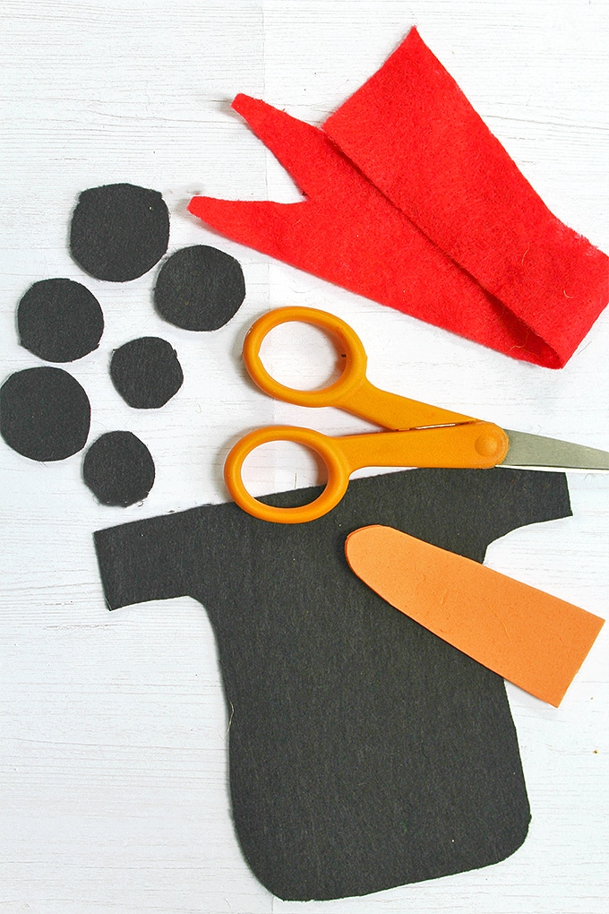 cut out black, red and orange felt and scissors to decorate snowman wood board decor