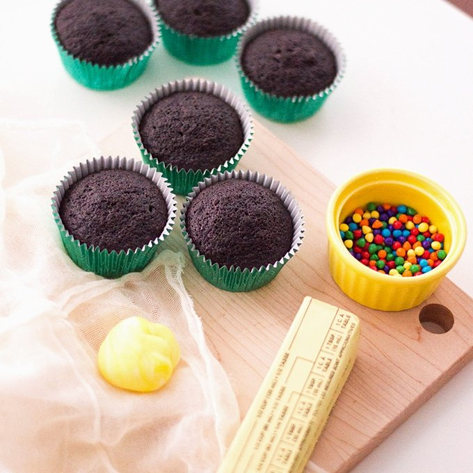 chocolate cupcakes, yellow fondant, butter, piping bag, and candies on a wooden cutting board
