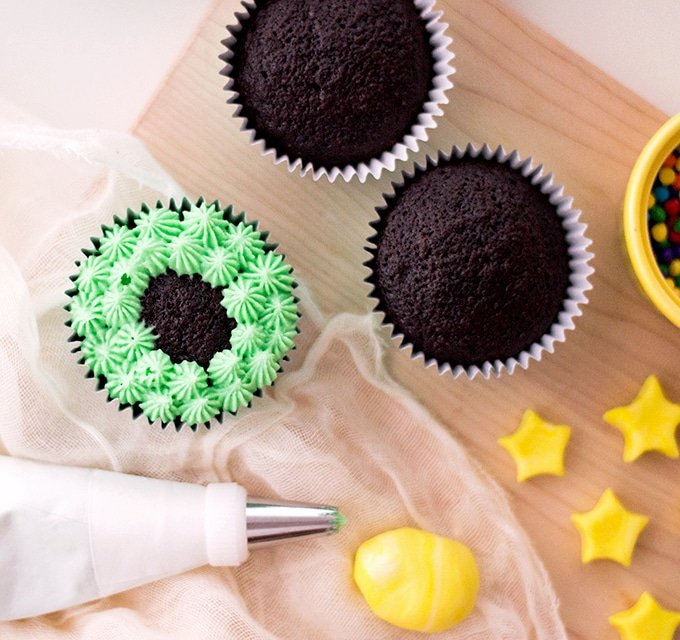 chocolate cupcakes piped with green frosting, piping bag, and yellow fondant stars