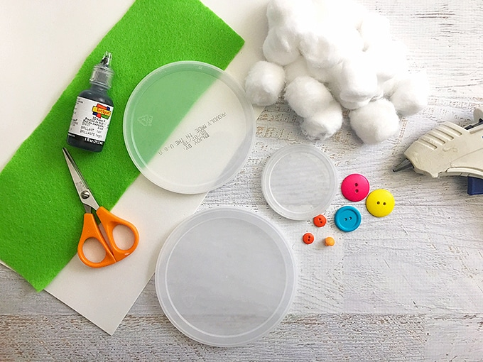 plastic lids, cotton balls, buttons, scissors, and green felt for cotton ball snowman craft