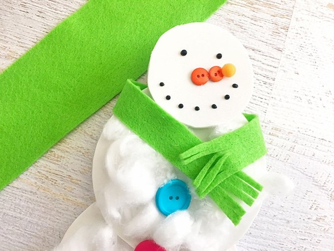 wrap and glue a green felt strip around snowman cotton ball craft to resemble a scarf