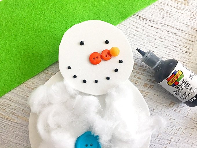 small orange buttons glued on snowman cotton ball craft to make the nose
