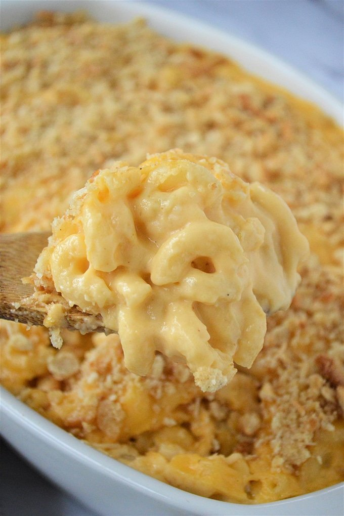 serving mac and cheese with a wooden spoon from a white casserole