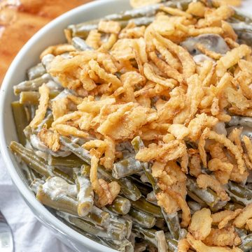 Slow Cooker Green Bean Casserole topped with french fried onions in a white serving bowl