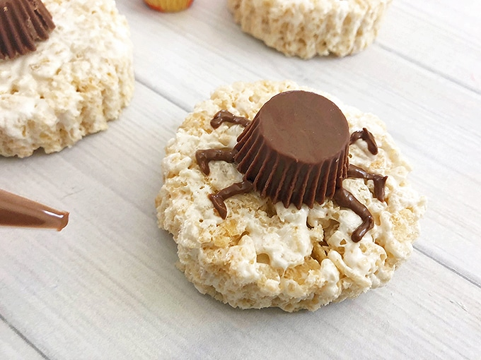"peanut butter cup with chocolate ""legs"" on round rice krispies treats to resemble spooky spider"