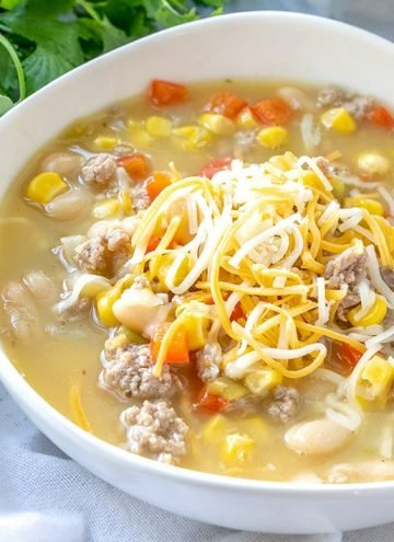 turkey and white bean chili topped with shredded cheese in a white bowl