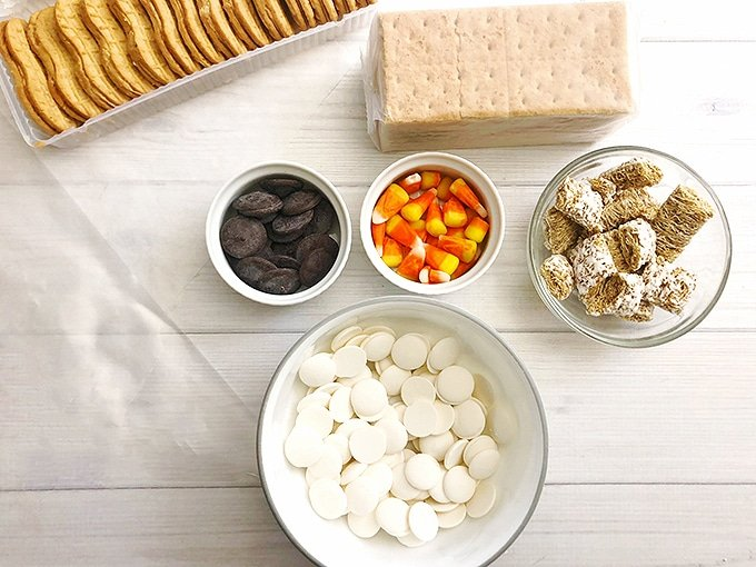 Nutter butters, candy corn, graham crackers, white candy melts, cocoa candy melts, frosted mini-wheats on a white board
