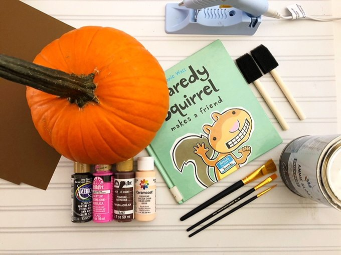pumpkin, assorted craft paints, paintbrushes, hot glue gun, cardstock paper, and scaredy squirrel book