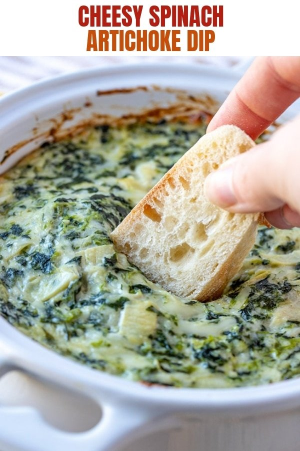 dipping sliced sourdough bread in spinach artichoke dip