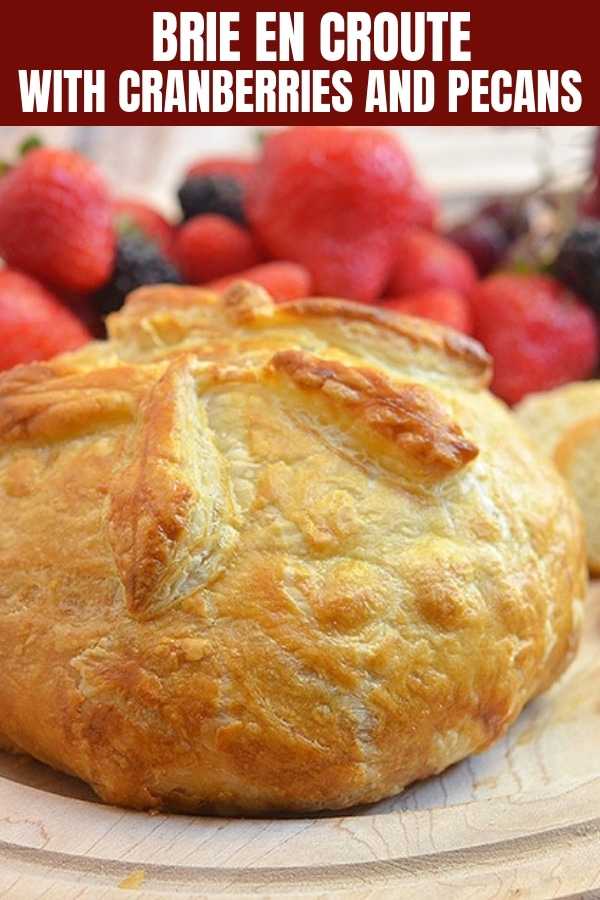 Brie en Croute on a wooden board with fresh fruits