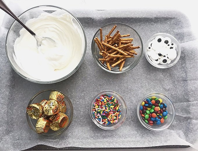 melted white candy melts, candy eyes, mini peanut butter cups, pretzel sticks, mini M&M's on a parchment-lined baking sheet to make snowman candy bark