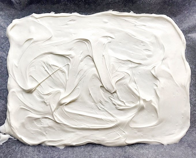 melted white chocolate spread on baking sheet to make candy bark