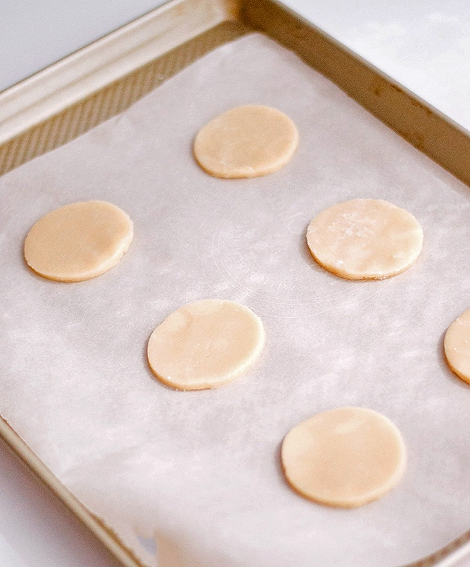 cut out sugar cookie dough on parchment-lined baking sheet