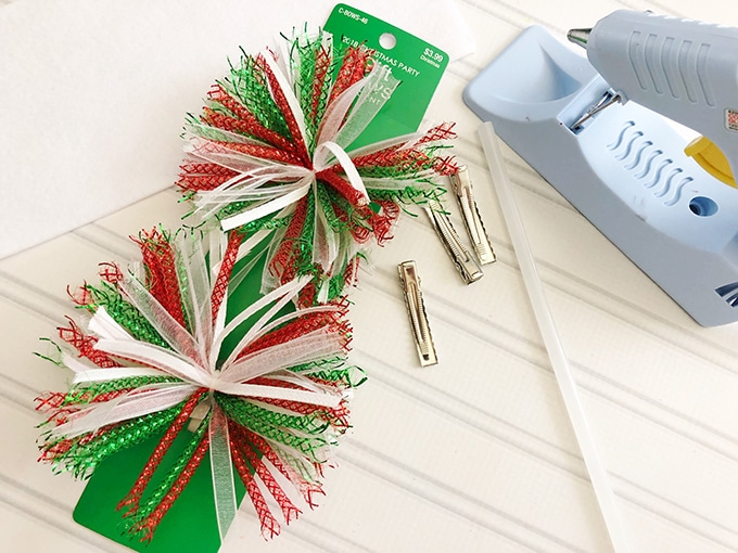 party gift bows, alligator clips, glue gun on a white board for making Christmas hair bows