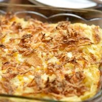 funeral potatoes baked in a clear casserole dish with french fried onion topping