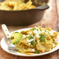 Chilaquiles with Salsa Verde on a white plate with chopped onion and cilantro garnish