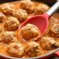 serving beef meatballs in tomato gravy with a spoon