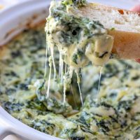 scooping cheesy spinach artichoke dip with baguette slices