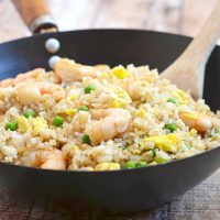 Fried Rice with shrimp, eggs, and green peas in a wok